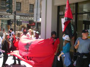 7 personnes font une ligne de piquetage devant un starbucks en tenant une bannière de la IWW
